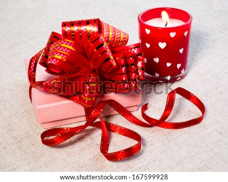 gift and candles in the shape of hearts reflected in a shiny background