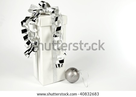 Gift bag with ribbon on a white and silver Christmas tree ball