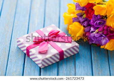 Gift box and bouquet of flowers on blue wooden table.
