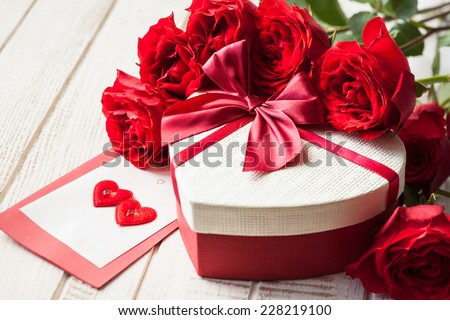 Gift box and bouquet of roses for holiday on wooden background. - stock photo