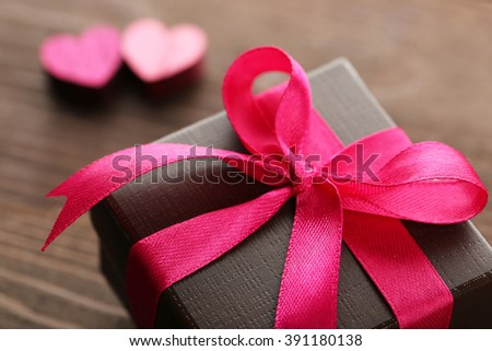 Gift box and decorative hearts on wooden background - stock photo