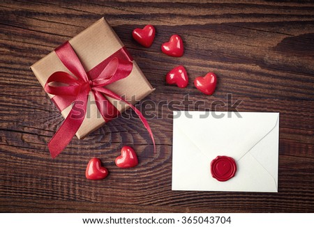 Gift box and love letter on wooden background from top view