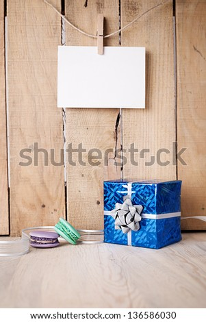 gift box and macaroons on a wooden table in front of a wooden wall with blank paper hanged - stock photo