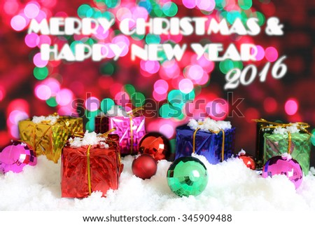 Gift box and ornament on snow and bokeh background, text of Merry Christmas and Happy New year 2016