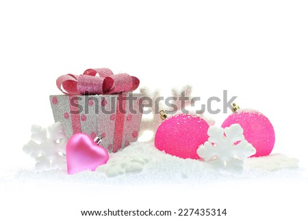 Gift box and pink Christmas ornaments on snow - stock photo