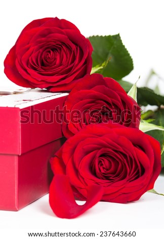 Gift box and red roses on white background