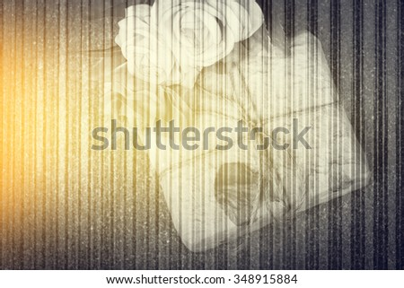 gift box and rose with metal sheet background ,black and white tone with yellow light - stock photo