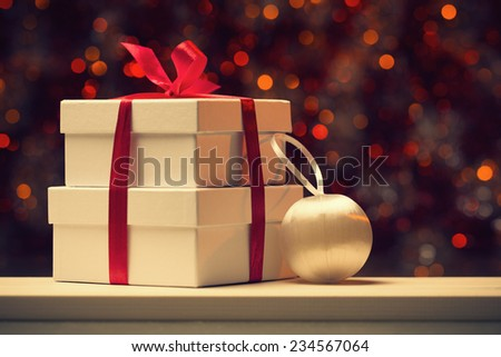 Gift box and xmas decoration against defocused lights - stock photo
