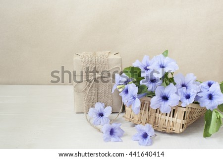 Gift box beautiful bouquet of bright purple flowers in basket on wooden table,vintage tone.   - stock photo
