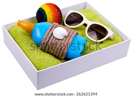 Gift box - blue plastic bottle of some liquid cosmetics, white sunglasses, ball for footbag game are on green towel. Decorated with rope and shell. Isolated. - stock photo
