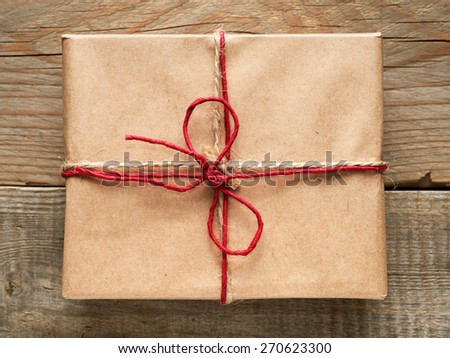 Gift box close-up top view on wooden background - stock photo