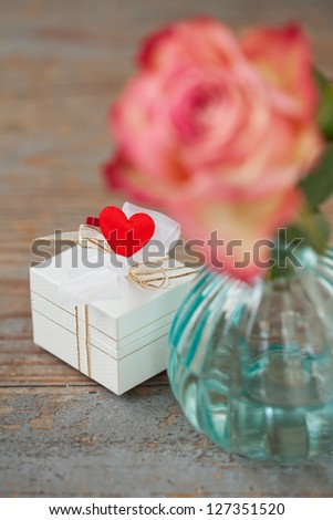 Gift box decorated with heart on wooden background - stock photo