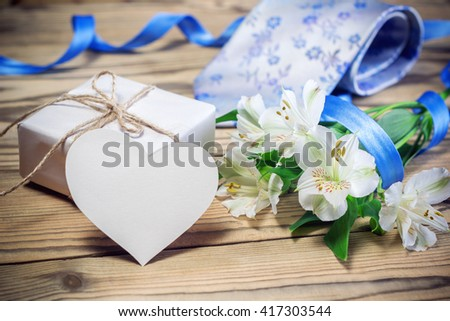 Gift box, flowers, card, ribbon and tie on a wooden table, with copy space.  - stock photo