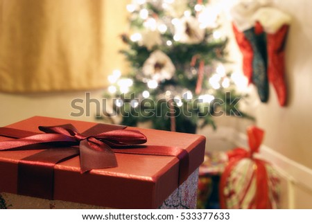 Gift box focused with Christmas tree blurred behind.