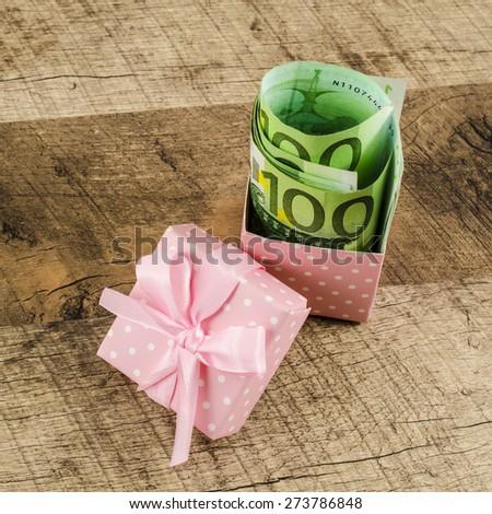 Gift box full of money on wooden table - stock photo