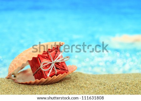 Gift box in a sea shell on the beach - stock photo