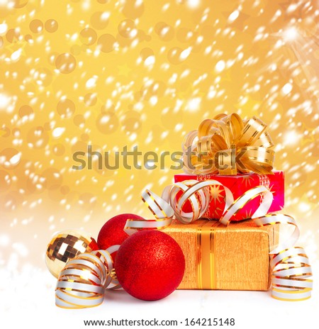Gift box in gold wrapping paper on a beautiful abstract background - stock photo