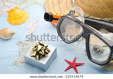 Gift box on a map with snorkel mask, seashells and starfish - stock photo