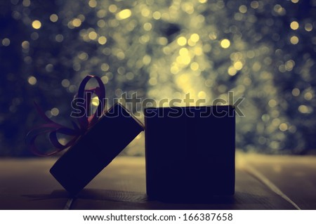 Gift box on abstract background in dark tonality - stock photo