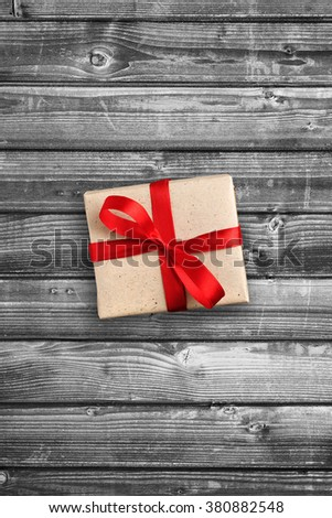 Gift box on black and white wooden background - stock photo