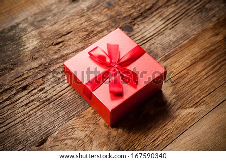 Gift box on old wooden table - stock photo