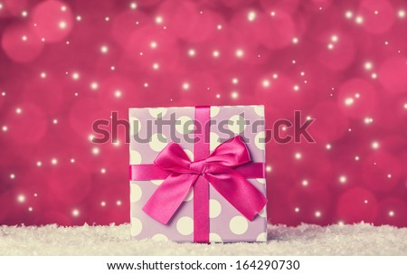 Gift box on snow and red background - stock photo
