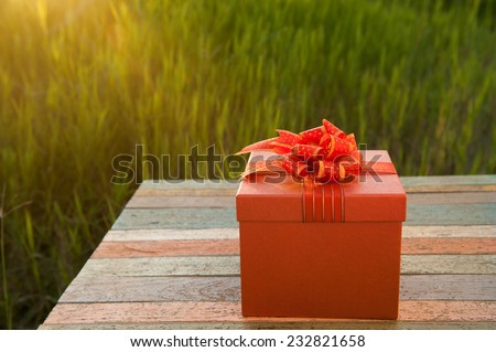 Gift box on wood table in sunset - stock photo