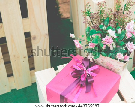 Gift box on wood table with flower for background,vintage style
