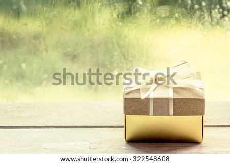 Gift box on wooden table on rainy day window background,vintage filter