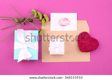 gift box (package) with blank gift tag on pink background and flowers, handmade heart. - stock photo
