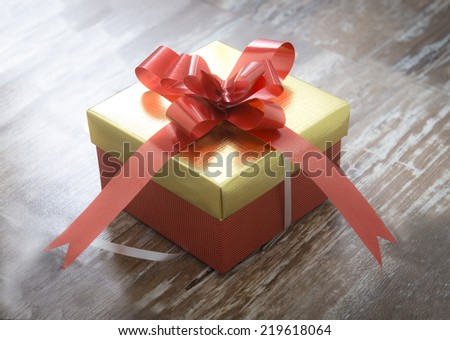 Gift box presents wrapped in red paper on wood background - stock photo