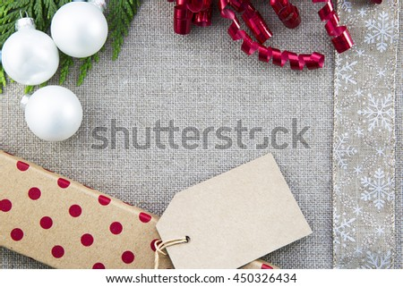 Gift box, ribbons and Christmas ornaments  on linen creating frame with copy space in center.