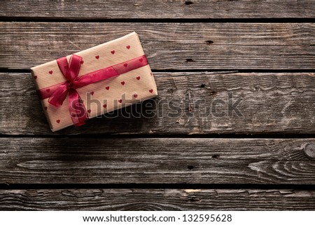 Gift box tied red ribbon with small red hearts printed on it. On old wooden background. - stock photo