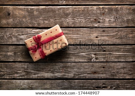 Gift box tied red ribbon with small red hearts printed on it. On old wooden background.