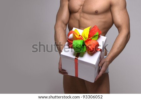 gift box with a beautiful ribbon in the hands of a strong muscular men - stock photo