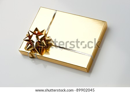 Gift box with a golden bow and ribbon