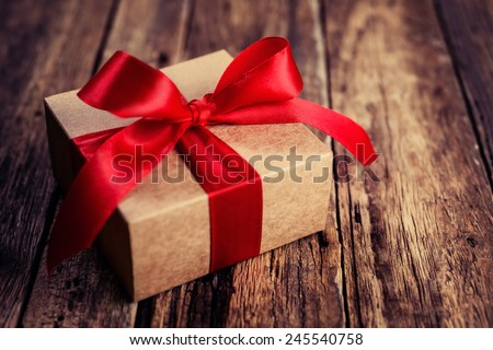 Gift box with a red ribbon on a wooden background, Valentines Day - stock photo