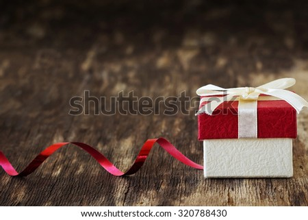 gift box with a ribbon on the old wooden background. festivals and events. selective focus. copy space background - stock photo