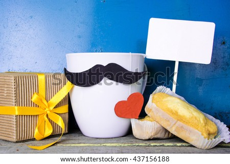 Gift box with a tag and a cup of coffee (tea), red heart, special cupcake and bow tie on wooden table. pad for text. - stock photo