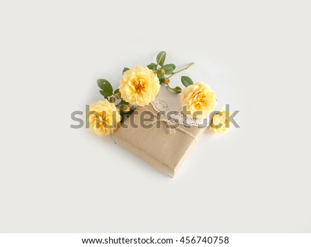 Gift box with beautiful yellow English rose on white background
