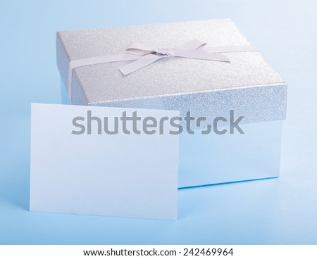 Gift box with blank envelope on a blue background - stock photo