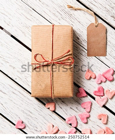 Gift box with blank gift tag and heap of small hearts on white wooden background. - stock photo
