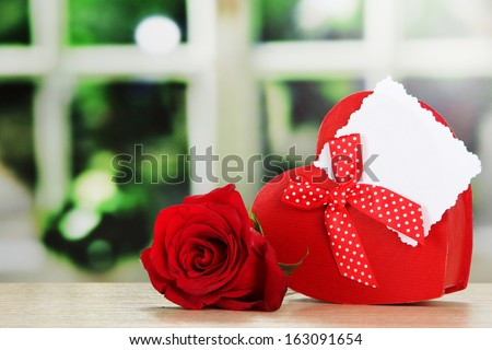 Gift box with blank label and rose on table on bright background