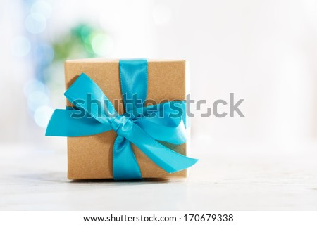 Gift box with blue ribbon in white wall room - stock photo