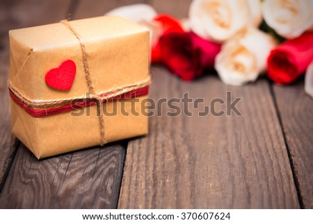 Gift box with blured red and white roses on a dark wooden background. Women' s day, Valentines Day, Mothers day. Copy space, selective focus. Natural optical blur, toned