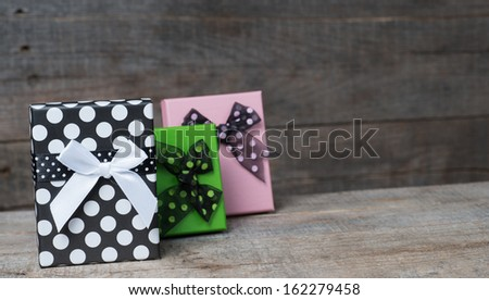 Gift box with bow on wood background - stock photo