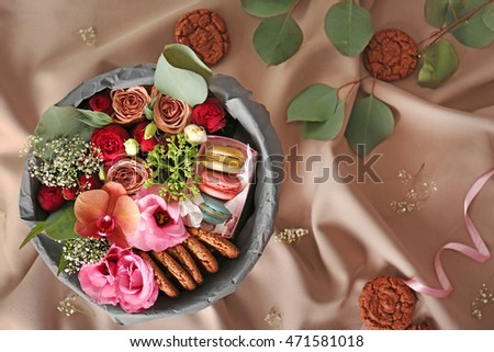 Gift box with flowers and cookies on cloth background