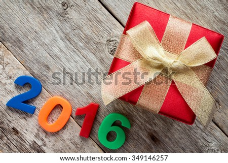 Gift box with gold ribbon  and a 2016 sign on wooden background