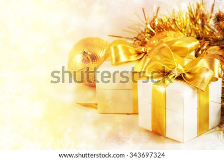 Gift box with golden ribbon and light christmas background. Card or invitation. - stock photo