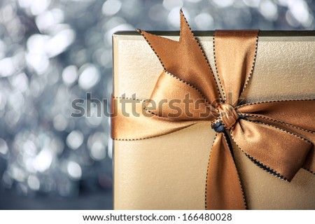 gift box with golden ribbon, glittery blue background - stock photo